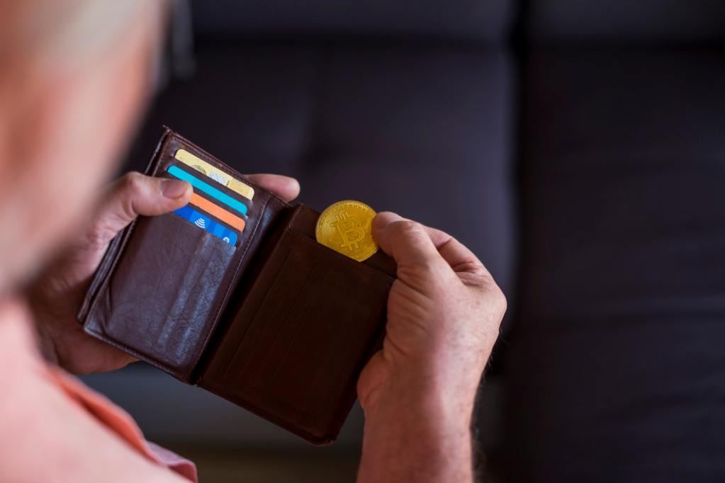 senior taking a gold bitcoin of his wallet - indoor - future payment and money concept