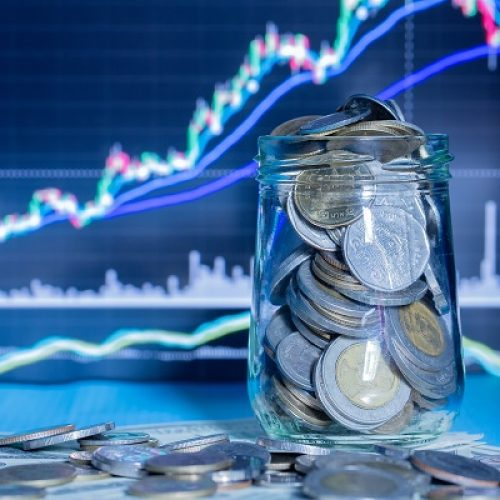 Coins in bottles with trading graph. financial investment concept use for background.
